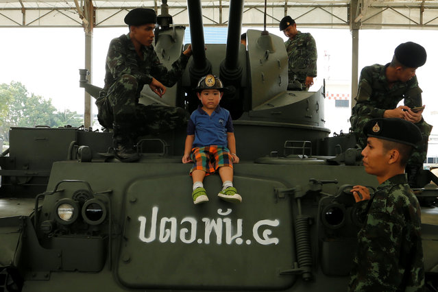 A boy sits on a tank to pose for a picture during Children's Day celebration at a military facility in Bangkok, Thailand January 14, 2017. (Photo by Jorge Silva/Reuters)
