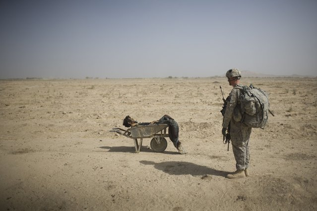 A U.S. Army soldier from Scout Platoon 502 Infantry Regiment, 101st Airborne Division, looks at the body of a suspected Taliban IED emplacer who was killed in a coalition missile strike in Zhari district, Kandahar province, Sunday, October 10, 2010. The Scouts' mission was to support roadside bomb clearance efforts in the militant stronghold, the latest days-long phase of Operation Dragon Strike. (Photo by Rodrigo Abd/AP Photo)