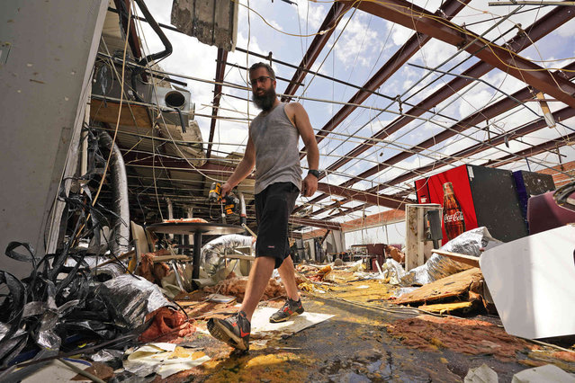 Jason Ledet relieves a tool as he works in a destroyed bowling alley as they try to recover from the effects of Hurricane Ida Tuesday, August 31, 2021, in Houma, La. (Photo by Steve Helber/AP Photo)