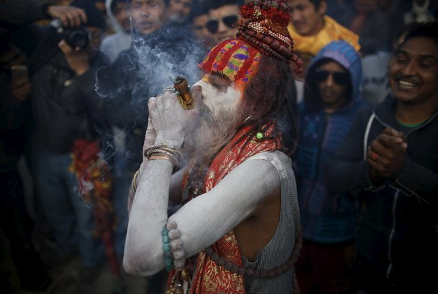 A Hindu holy man, or sadhu, smeared with ashes smokes marijuana in a chillum during the Shivaratri festival on the premises of Pashupatinath Temple in Kathmandu, Nepal, March 7, 2016. Hindu holy men from Nepal and India come to this temple to take part in the Maha Shivaratri festival. Celebrated by Hindu devotees all over the world, Shivaratri is dedicated to Lord Shiva, and holy men mark the occasion by praying, smoking marijuana or smearing their bodies with ashes. (Photo by Navesh Chitrakar/Reuters)