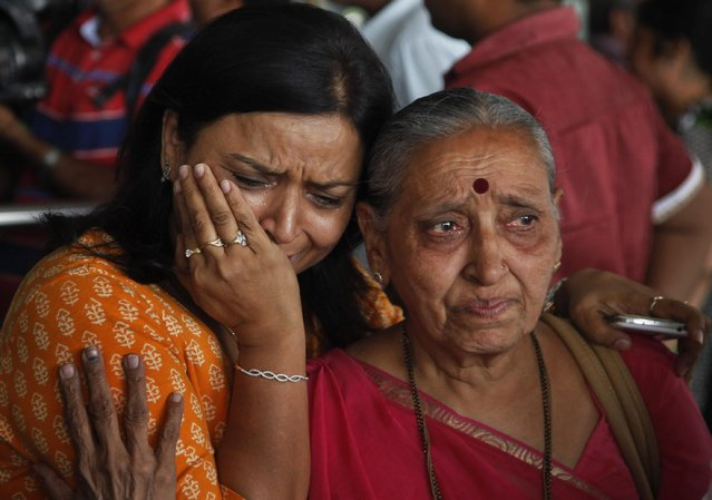 An Indian woman cries as her relative, right who was on pilgrimage in Nepal during Saturday's earthquake, returned at the airport in Ahmadabad, India, Monday, April 27, 2015. The earthquake was the worst to hit the South Asian nation in more than 80 years. It and was strong enough to be felt all across parts of India, Bangladesh, China's region of Tibet and Pakistan. (Photo by Ajit Solanki/AP Photo)