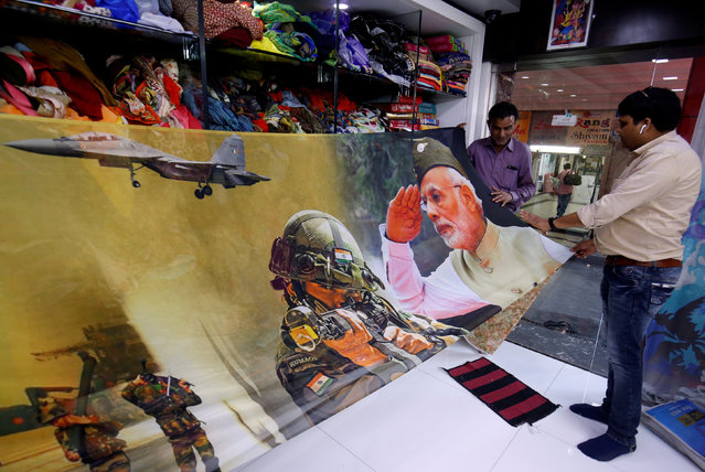 Traders display a sari, a traditional clothing worn by women, with printed images of India's Prime Minister and Indian Army inside their shop in Surat, India, March 8, 2019. (Photo by Amit Dave/Reuters)