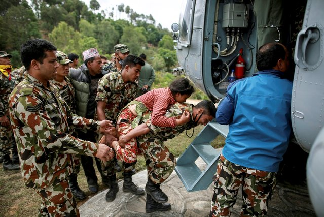 A Nepal Army personnel carries an injured woman to an Indian Airforce helicopter following Saturday's earthquake in Sindhupalchowk, Nepal, April 28, 2015. (Photo by Danish Siddiqui/Reuters)