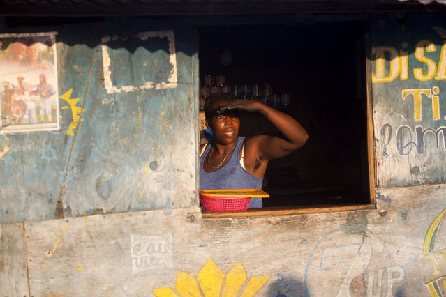In this December 5, 2016 photo, Adrienne St. Fume looks out from her vendor's stall where she sells milk, charcoal, oil and rice in the Delmas tent camp set up nearly seven years ago for people displaced by the 2010 earthquake, in Port-au-Prince, Haiti. Nearly seven years later, St. Fume's family is still stuck in the maze of shacks that's morphed into a crowded shantytown of dusty lanes in what was once a vacant lot in Port-au-Prince. (Photo by Dieu Nalio Chery/AP Photo)