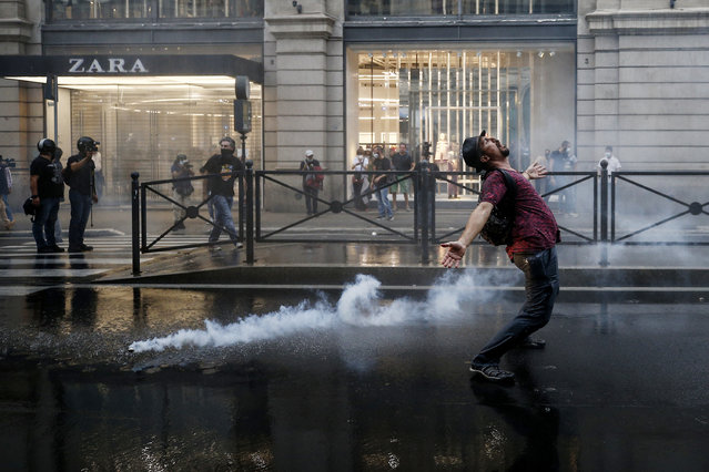 A demonstrator reacts as police fire teargas during a protest, in Rome, Saturday, October 9, 2021. (Photo by Cecilia Fabiano/LaPresse via AP Photo)