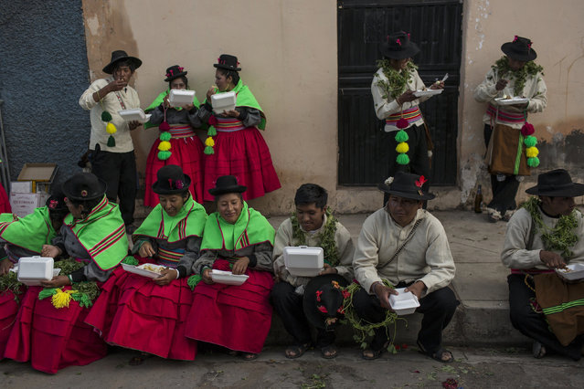In this January 29, 2017 photo, dancers eat lunch after performing during Virgin of Candelaria celebrations in Puno, Peru. In addition to adults, young children dance with their families in groups of as many as 400 people, including musicians who play flutes and other traditional instruments. (Photo by Rodrigo Abd/AP Photo)