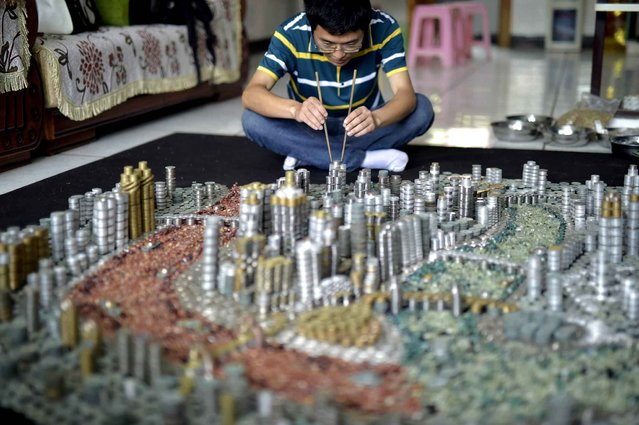 This photo taken on April 29, 2015 shows He Peiqi, a Chongqing local resident, building a replica of the city with coins and agate stones at his home in China's southwest Chongqing municipality. (Photo by AFP Photo/Stringer)