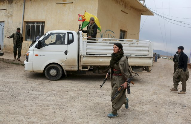Kurdistan Workers Party (PKK) fighters prepare to attend a military funeral for a Yazidi fighter from the YBS who was killed during fighting with Islamic State militants, in Sinjar, March 12, 2015. YBS are a Yazidi militant group, who are fighting against Islamic State. (Photo by Asmaa Waguih/Reuters)