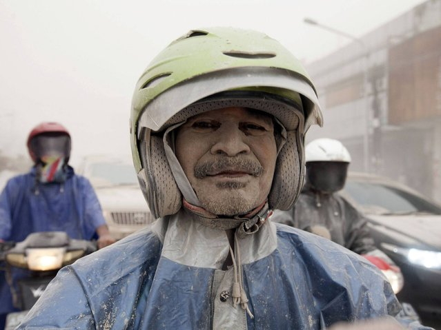 A man covered with ash from Mount Kelud is seen on his motorcycle in Yogyakarta. (Photo by Dwi Oblo/Reuters)