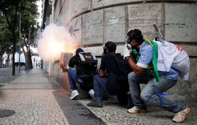 Anti-government demonstrators clash with riot policemen during a protest against the Rio de Janeiro state government and a plan that will limit public spending, next to the State Assembly of Rio de Janeiro, Brazil February 9, 2017. (Photo by Ricardo Moraes/Reuters)