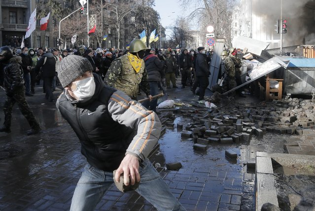 Anti-government protesters lob stones during clashes with riot police outside Ukraine's parliament in Kiev, Ukraine, Tuesday, February 18, 2014. Some thousands of angry anti-government protesters clashed with police in a new eruption of violence Tuesday. (Photo by Efrem Lukatsky/AP Photo)