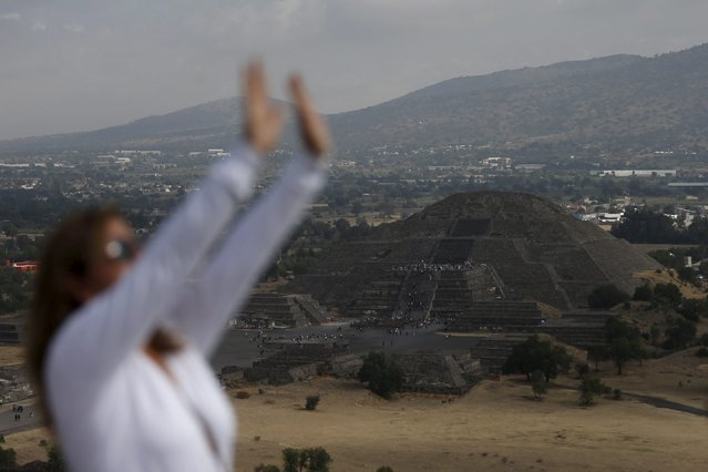 A view of the Pyramid of the Moon is seen in the background while a woman raises her arms towards the sun to welcome the spring equinox in the pre-hispanic city of Teotihuacan on the outskirts of Mexico City, Mexico, March 20, 2016. (Photo by Edgard Garrido/Reuters)