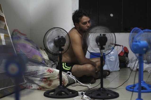 A Cuban migrant cools himself with fans inside a room of an old hotel used as a provisional shelter in Paso Canoas, at the border with Costa Rica, in Panama March 21, 2016. (Photo by Carlos Jasso/Reuters)