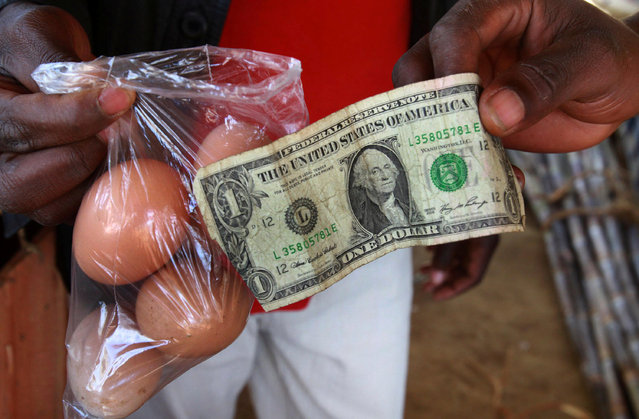 A man buy eggs using a U.S. one dollar bill at a market in Harare, Zimbabwe on June 17, 2010. (Photo by Philimon Bulawayo/Reuters)