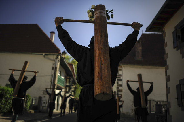 "Masked penitents holds their crosses during spring ""Romeria Cruceros de Arce"", in Roncesvalles, northern Spain, Sunday, May 10, 2015. (Photo by Alvaro Barrientos/AP Photo)"