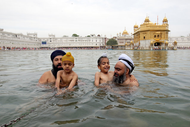 Sikh men and children take a holy dip in the sacred pond of the Golden Temple, the holiest of Sikh places on the occasion of the Visakhi festival in Amritsar, India, 14 April 2019. In 1699 AD, Guru Gobind Singh ji, the tenth Sikh Guru, or Master, organized the Sikhs under one order called the Khalsa Panth commemorated as the Visakhi Festival which also marks the beginning of the Sikh New Year. The day is celebrated with religious fervor and zeal by the people of Punjab. (Photo by Raminder Pal Singh/EPA/EFE)