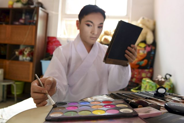 Folk opera performer Guo Jiafu applies make-up at a bedroom before a performance for a man's 80th birthday celebration, in Taiyuan, Shanxi province, China, May 7, 2015. Guo, a 29-year-old man, made his name heard in the folk opera field in Shanxi and neighbouring provinces by his cross-dressing performances. He has been practicing playing female roles in folk opera for 16 years, local media reported. (Photo by Reuters/Stringer)