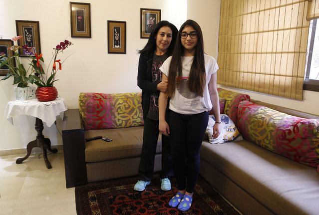 Rima Bader, 44, poses with her daughter Reina, 13, inside their apartment in Beirut February 25, 2014. Rima is an interior designer but she says that when she was growing up she wanted to be an engineer. Rima wants her daughter to work in whatever profession she chooses, but she says she would love to see her in the field of engineering. Reina says she will finish education when she is around 21 years old. She wants to be an architect when she grows up. (Photo by Jamal Saidi/Reuters)