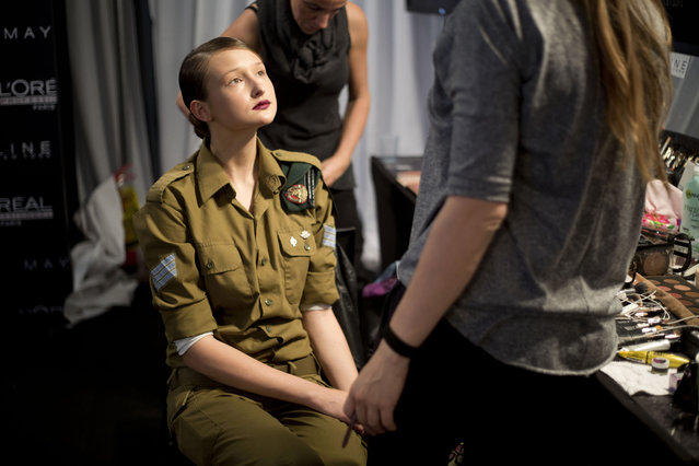 An Israeli model, who serves in the military, wears her uniform in the makeup chair before her turn on the catwalk a show by Israeli designer Dorin Frankfurt at the Tel Aviv fashion week, Israel, Tuesday, March 11, 2014. (Photo by Ariel Schalit/AP Photo)