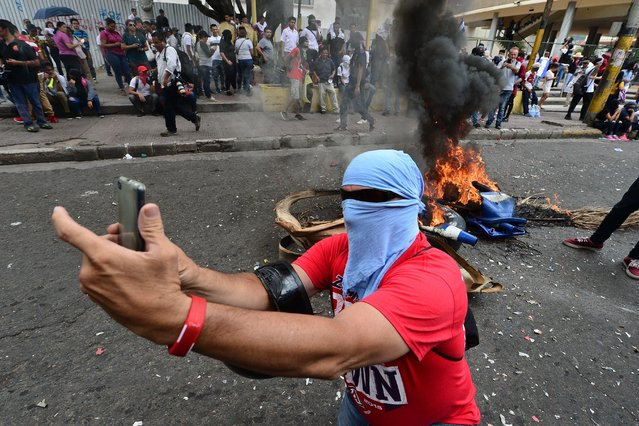 A student makes a selfie next to a bonfire during a protest against Honduran President Juan Orlando Hernandez in the surroundings of the Congress building in Tegucigalpa, on May 22, 2019. The students demand the Congress to derogate at leat 11 decrees regarding health and education. (Photo by Orlando Sierra/AFP Photo)