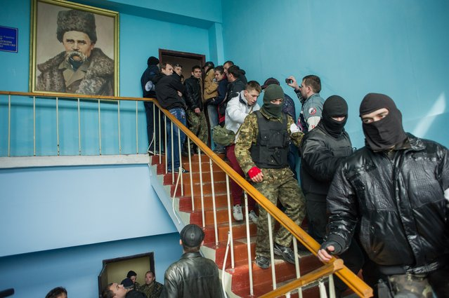 Crimean pro-Russian self-defense forces walk through the Ukrainian navy headquarters, with a picture of 19th century Ukrainian poet and writer Taras Shevchenko, in Sevastopol, Crimea, Wednesday, March 19, 2014. Crimea's self-defense forces on Wednesday stormed the Ukrainian navy headquarters in the Black Sea port of Sevastopol, taking possession without resistance a day after Russia signed a treaty with local authorities to annex the region. (Photo by Andrew Lubimov/AP Photo)