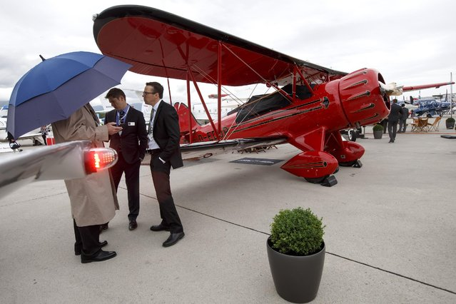 Visitors stand next to a WACO aircraft during the 15th Annual European Business Aviation Convention and Exhibition, EBACE, at the Geneva Palexpo Conference Center located adjacent to the Geneva Airport in Geneva, Switzerland, Tuesday, May 19, 2015. (Photo by Salvatore Di Nolfi/Keystone via AP Photo)