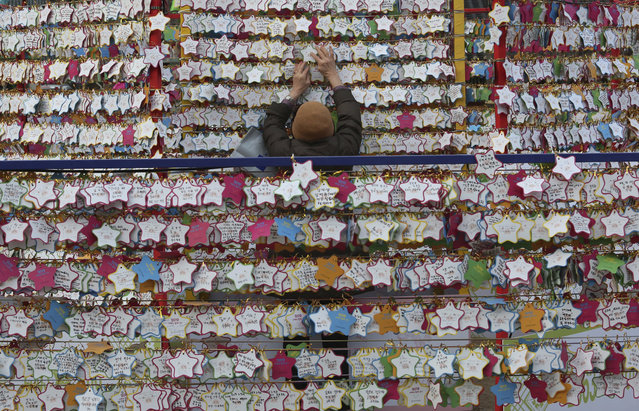 In this Monday, December 31, 2018, file photo, a woman hangs paper notes bearing her New Year wishes outside the Jogyesa Buddhist temple in Seoul, South Korea. (Photo by Ahn Young-joon/AP Photo)