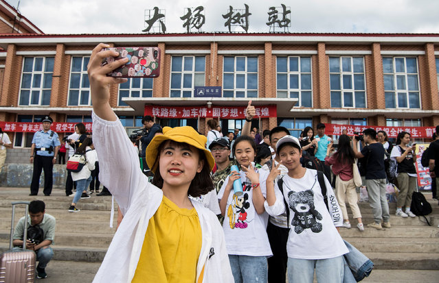 """Students take photos as they wait for a """"gaokao train"""" at Dayangshu township on June 5, 2019 in the Inner Mongolia Autonomous Region, China. The special train operates only once a year and takes 450 students from Dayangshu of North China's Greater Hinggan Mountains to Alihe, a town 135 kilometers away. Dayangshu lies in the southern part of Inner Mongolia's Greater Hinggan Mountains and is inhabited by Oroqen, Daur and Ewenki ethnic groups. The town is too small to have its own test center, so students travel to Alihe for the gaokao. Gaokao, the national college entrance examination, takes place on June 7 and 8 and determines which universities students can go to. More than 10 million students have registered this year, Minister of Education Chen Baosheng said. (Photo by Tao Zhang/Getty Images)"""