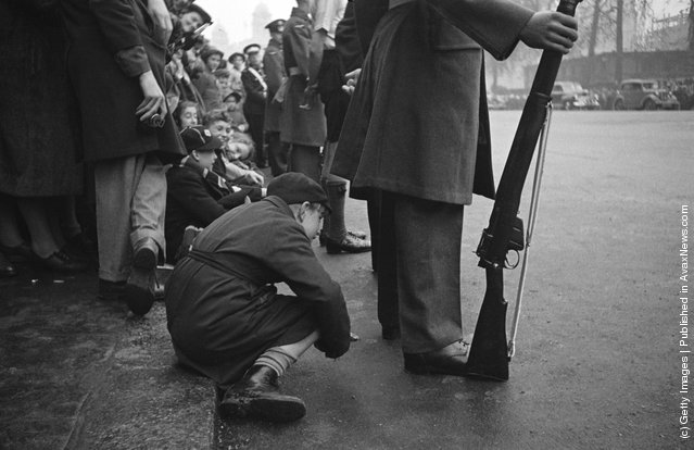 A boy peers under the legs of an RAF serviceman for a glimpse of the wedding procession of Princess Elizabeth (later Queen Elizabeth II) and Philip Mountbatten, Duke of Edinburgh, London, 20th November 1947
