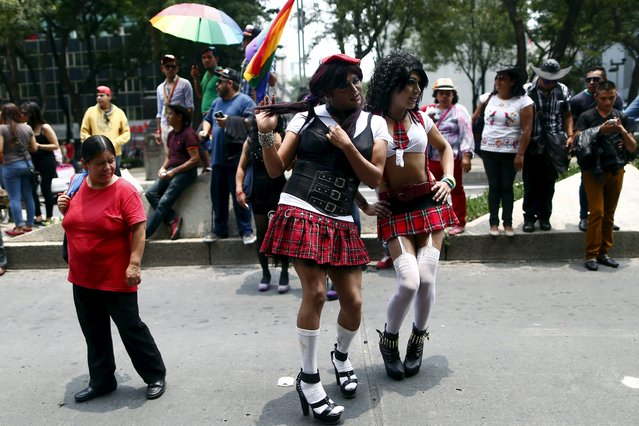 Participants pose for a photo as a woman looks at them while they march during a Gay Pride Parade in Mexico City, June 27, 2015. Thousands of LGBT (lesbian, gay, bisexual and transgender) rights activists participated in the annual parade throughout Mexico City, according to local media. (Photo by Edgard Garrido/Reuters)