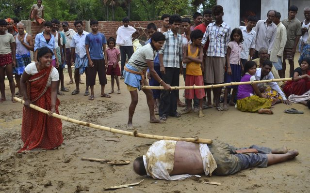 In this Sunday, June 28, 2015 photo, and Indian man and a woman strike the body of a school director with sticks as it lies on the ground in Nirpur village, about 90 kilometers (55 miles) southeast of Patna, the capital of Bihar state, India. Police are investigating the mob killing of the school director in northern India after two of the school's students aged 10 and 11, were discovered dead in a nearby pond, officials said Monday. (Photo by AP Photo/Stringer)