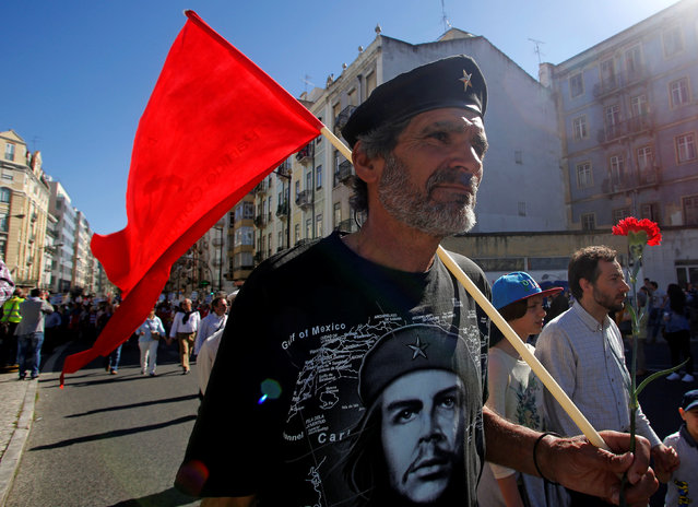 A man holds a flag and carnation during a May Day march by the Portuguese union CGTP in Lisbon, Portugal, May 1, 2016. (Photo by Hugo Correia/Reuters)