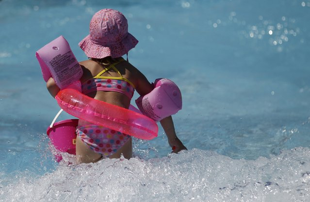 """A young girl cools off from the heat at """"Grugabad"""" open-air swimming pool on a hot summer day in Essen, Germany, June 30, 2015. A widespread, long-lasting heat wave will spread across much of France, U.K., Belgium, the Netherlands and western Germany with forecast highs on Wednesday reaching 35 degrees Celsius (95 degrees Fahrenheit). (Photo by Ina Fassbender/Reuters)"""