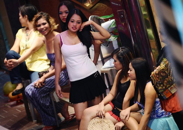 Female entertainers gather at a bar doorway in Hong Kong's notorious Wan Chai bar and club district on September 5, 2009. The old style gogo bars of Wan Chai, where lithe young women entice customers to buy them overpriced drinks, are the places most commonly associated with Hong Kong's the s*x trade. Immortalized as the seedy but romantic World Of Suzie Wong in the novel by Richard Mason, 1950s Wan Chai originally became famous for its drunken sailors and prostitutes. (Photo by AFP Photo/Stringer)