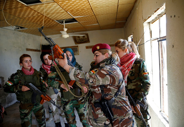 Iraqi Kurdish female fighter Haseba Nauzad (2nd R), 24, holds her weapon as she is surrounded by comrades at a site during a deployment near the frontline of the fight against Islamic State militants in Nawaran near Mosul, Iraq, April 20, 2016. (Photo by Ahmed Jadallah/Reuters)