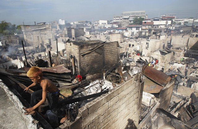 A boy climbs out of a charred shanty as he collects reusable materials after a fire razed through a slum area in Caloocan City, Metro Manila April 21, 2014. The fire left one dead and displaced an estimated 1,000 families and at least 400 houses were destroyed during the fire, a local media reporte. (Photo by Romeo Ranoco/Reuters)