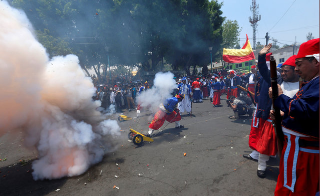 Mexicans wearing period costumes, fire a cannon during a re-enactment of the battle of Puebla, in the Penon de los Banos neighbourhood of Mexico City, Mexico, May 5, 2016. (Photo by Henry Romero/Reuters)