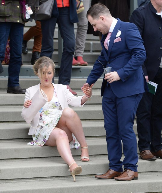 Another woman is helped up by a friend on the stairs during the Grand National Festival at Aintree Racecourse on April 6, 2017 in Liverpool, England. (Photo by News Group Newspapers Ltd)