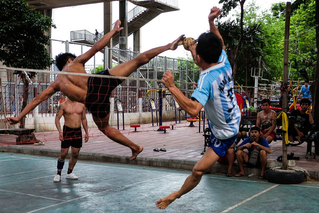 Men play a game of sepak takraw in Bangkok, Thailand on July 7, 2019. Sepak takraw use of a rattan ball and only allowing players to use their feet, knee, chest and head to touch the ball. (Photo by Candida N.G./AFP Photo)