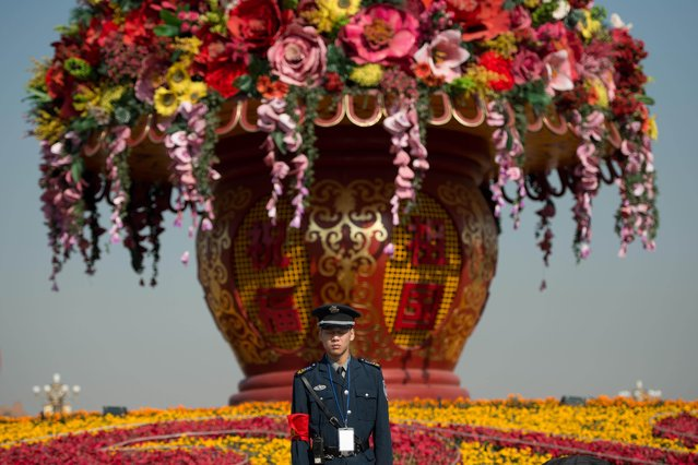 A security guard stands before a floral display on Tiananmen Square in Beijing on November 1, 2012. The Communist Party's Central Committee convened behind closed doors, state media said, with 500 senior members brought together ahead of a congress which will open on November 8 to usher in leaders for the next decade. (Photo by Ed Jones/AFP Photo)