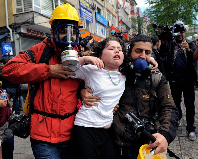 People help a child affected by teargas as police use water cannons and teargas to disperse thousands of people trying to reach the city's main Taksim Square to celebrate May Day in Istanbul, on May 1, 2014. Clashes erupted between demonstrators and police as crowds determined to defy a government ban tried to march to the city's iconic square. (Photo by Emrah Gurel/Associated Press)