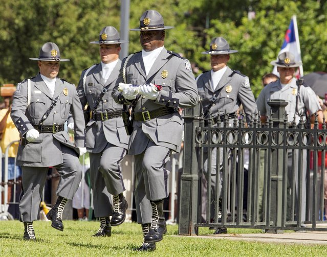 "Honor guard removes the Confederate battle flag permanently from the South Carolina statehouse grounds during a ceremony in Columbia, South Carolina, July 10, 2015. South Carolina removed the Confederate battle flag from the state capitol grounds on Friday to chants of ""USA, USA!"", after three weeks of emotional debate over the banner, a symbol of slavery and racism to many, but of Southern heritage and pride to others. (Photo by Jason Miczek/Reuters)"