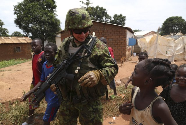 An Estonian soldier from a newly deployed European Union military operation in the Central African Republic jokes with children as he patrols along a street in Bangui, on May 8, 2014. (Photo by Emmanuel Braun/Reuters)