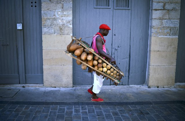 A musician wearing a red beret carries a percussion instrument on the seventh day of the San Fermin festival in Pamplona, northern Spain, July 12, 2015. (Photo by Vincent West/Reuters)