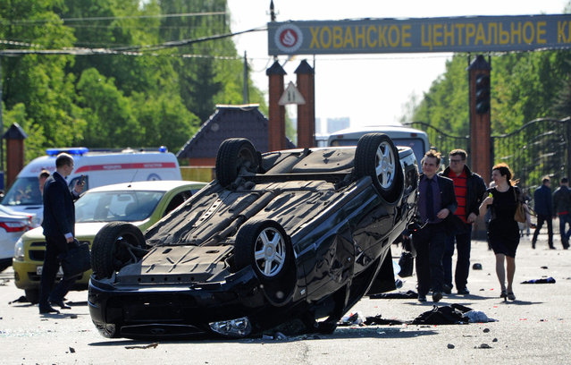 A car lays overturned after a mass brawl at the Khovanskoye cemetery in Moscow, Russia, 14 May 2016. At least two people were killed in a mass brawl at the cemetery in southwest Moscow, while 50 people were arrested, Russian police said. Several hundreds of migrants said of Central Asian and Caucasians ethnic groups took part in the brawl using shovels, baseball bats and even firearms, according to officials from Russian interior ministry. It is believed that the opposing ethnic groups tried to take under their control the cemetery service business. (Photo by Vladimir Velengurin/EPA/Komsomolskaya Pravda)