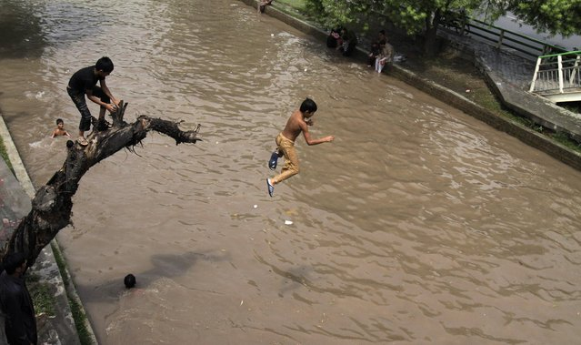 A Pakistani youngster jumps into a canal to beat the heat as temperature reached 41 degrees Celsius (105.8 Fahrenheit) in Lahore, Pakistan, Sunday, July 5, 2015. Many cities in Pakistan are facing heat wave conditions with temperatures reaching up to 47 degrees Celsius (116.6 Fahrenheit) in some places. (Photo by K. M. Chaudary/AP Photo)