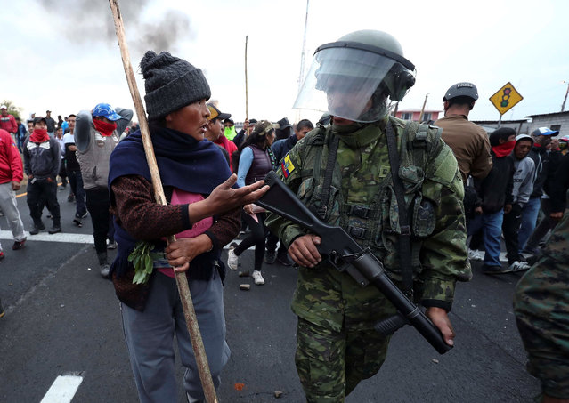 Military try to control the protests of the indigenous people who demonstrate during a new day of protests against the measures decreed by the Government of Lenin Moreno after an agreement with the International Monetary Fund (IMF), in the town of Lasso, province of Cotopaxi, Ecuador, 06 October 2019. (Photo by Jose Jacome/EPA/EFE)