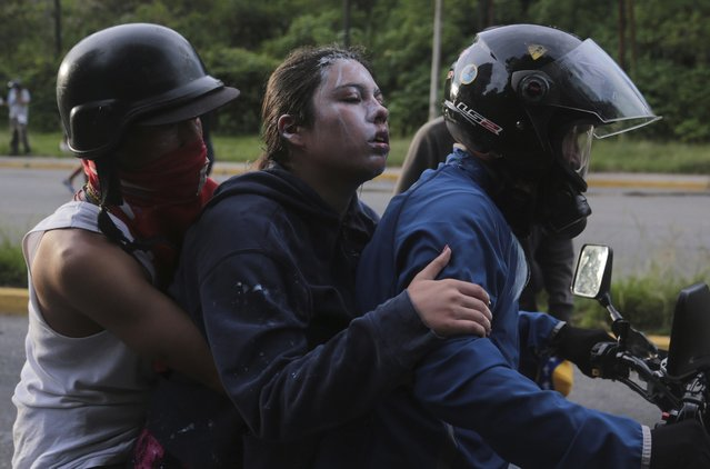 A demonstrator affected by tear gas is evacuated during clashes with the Bolivarian National Guard, at El Hatillo municipality outside Caracas, Venezuela, Tuesday, May 2, 2017. People blocked streets in Caracas with broken concrete, twisted metal and flaming piles of trash to protest the president's bid to rewrite the constitution amid a rapidly escalating political crisis. (Photo by Fernando Llano/AP Photo)