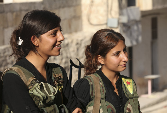 "Kurdish fighters from the Popular Protection Units (YPG), wearing vests with the YPG logo, stand along a street in Aleppo's Sheikh Maqsoud neighborhood, June 19, 2013. Kurdish fighters from the Popular Protection Units (YPG) joined the ""Free Syrian Army"" to fight against forces loyal to Syria's President Bashar al-Assad. (Photo by Nour Kelze/Reuters)"