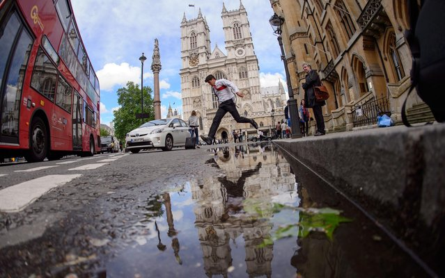 A person jumps over a wide puddle in front of Westminster Abbey following heavy rain in central London, on May 22, 2014. (Photo by Leon Neal/AFP Photo)